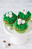 Easter cupcakes with green frosting and sugar eggs on a cake stand