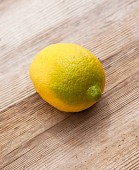 A combination of a lemon and a lime on an old wooden surface