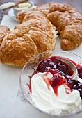 Strawberry jam and cream cheese in a glass bowl in front of two croissants
