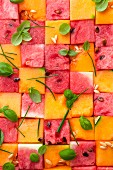 Pink and yellow diced melon with melon pips and basil leaves