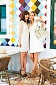 Zwei Frauen in weißen Sommerkleidern vor bunter Wand machen ein Selfie