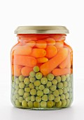 Peas and carrots in a jar on a white surface
