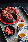 Chocolate cake with raspberries, sliced, with tea
