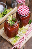 Tomato and celery drinks in screw-top jars with straws
