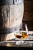 Glas Cognac neben altem Holzfass