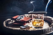 A smoking cigar over a glass of whiskey