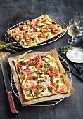 Tarte flambée with asparagus, sheep's cheese, Serano ham and tomatoes
