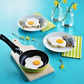 Fried egg and cutlery-shaped biscuits in a pan and on plates
