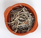 Glass eels in a terracotta bowl (seen from above)