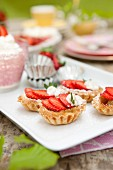 Strawberry tartlets with whipped cream and mint leaves