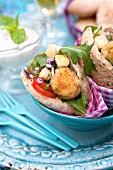 Pitabrote mit Falafel, Käse, Tomate, Zwiebeln und Rucola