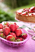 A basket of fresh strawberries with a strawberry cake in the background