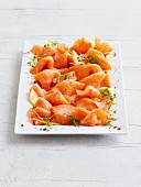 Smoked salmon with dill and lemon on a serving platter