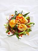 Jacobsmuscheln auf Pergamentpapier mit Mangold, roter Kresse und Passionsfrucht
