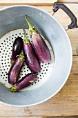 Freshly washed aubergines in a colander