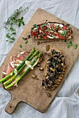 Various open sandwiches on a chopping board