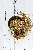 Freekeh in a bowl and on a wooden surface