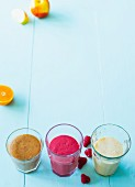 Three smoothies with almond mousse, plums, oranges and banana (Paleo)