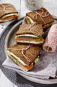 Wholemeal sandwiches with goats cheese, smoked salmon and avocado (Scandinavia)
