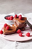 Heart-shaped ice cream sandwiches with stroopwaffels, chocolate ice cream and raspberries