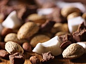 Pieces of coconut, fudge and almonds (close-up)