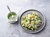 Green potato salad with ham and dressing