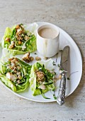 Chicken with a bread crust and vegetables in lettuce leaves served with coconut and peanut butter