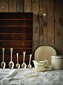 Sauciere und Silberlöffel auf weisser Tischdecke vor Holzwand