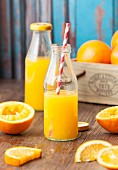 Two bottles of freshly pressed orange juice surrounded by oranges