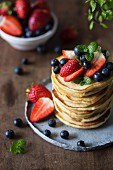 A stack of pancakes topped with fresh strawberries and blueberries (USA)