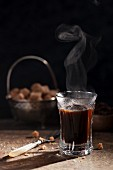 A glass of steaming black coffee with a bowl of sugar cubes in the background