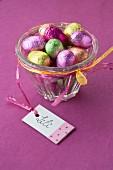 Schokoladenostereier in bunter Folie in Glasschale mit Geschenkanhänger