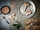 An arrangement of mushrooms, bay leaves, garlic and borlotti beans