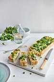 A tart topped with peas, cheese and pea shoots, sliced