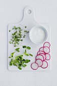 Pea shoots, cress and sliced radish with a pot of yoghurt