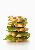 Ein Stapel veganer Waffeln mit Salatblättern vor weißem Hintergrund