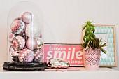 Verschiedene Weihnachtskugeln in Pastelltönen umhäkelt unter Vintage-Glasglocke mit rosafarbenem Emailleschild und Pflanze auf Ablage