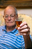 Elderly man with a glass of sherry