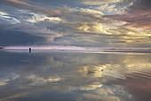 A couple on a vast sandy beach