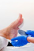 Scraping hard skin on a foot