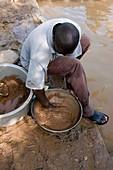 Artisan miner panning for gold,Kenya
