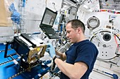 Astronaut cleaning ISS lab equipment