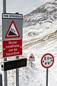 Massive snow drifts blocking a road