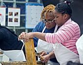 Volunteers uncapping honeycomb