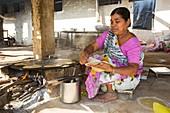 Woman preparing chapatis,India
