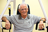 Active elderly man smiling in gym