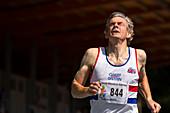 Masters athlete crossing finishing line