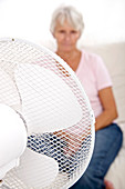 Older lady with an electric fan
