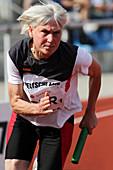 Determined female senior athlete running