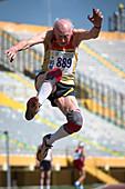 Elderly male athlete jumping mid-air